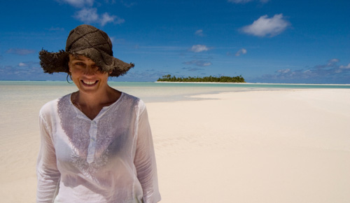 Woman wearing a hat smiling on the beach