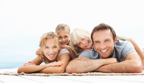 Portrait of happy kids lying over mature man and woman at the beach