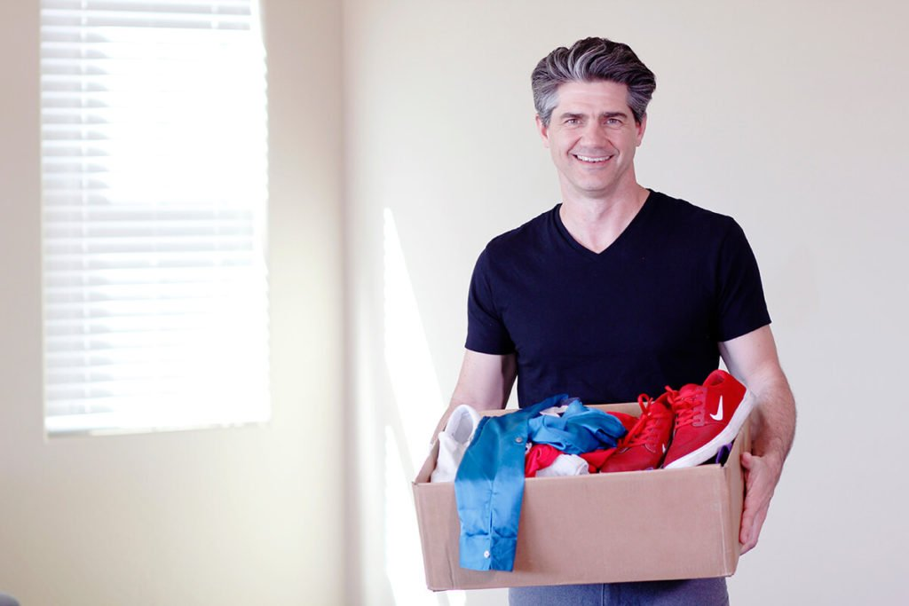 Joshua Becker, from Becoming Minimalist, smiling and holding a box, ready to teach readers how to declutter