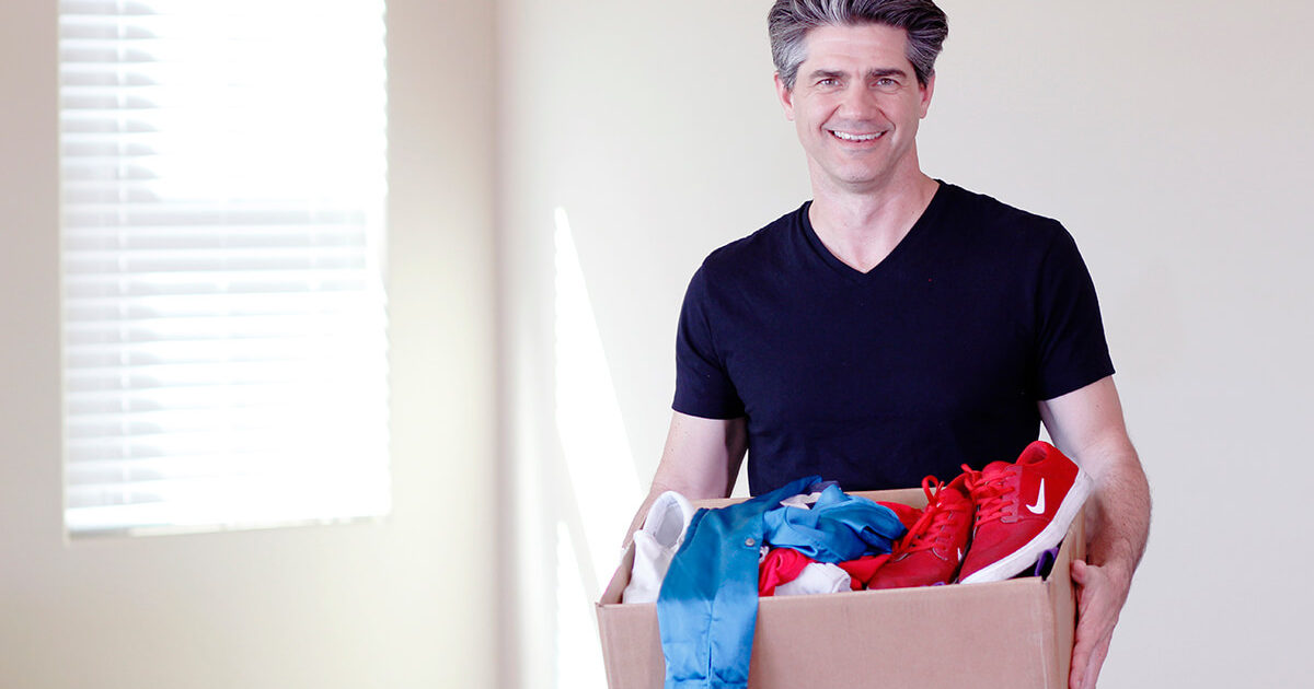 Joshua Becker, from Becoming Minimalist, holding a box of clothes and red shoes to be decluttered
