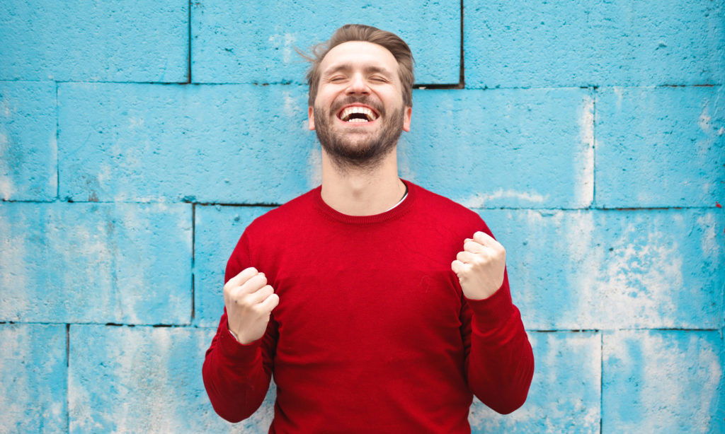 Man with eyes closed wearing a red sweater filled with happiness while smiling